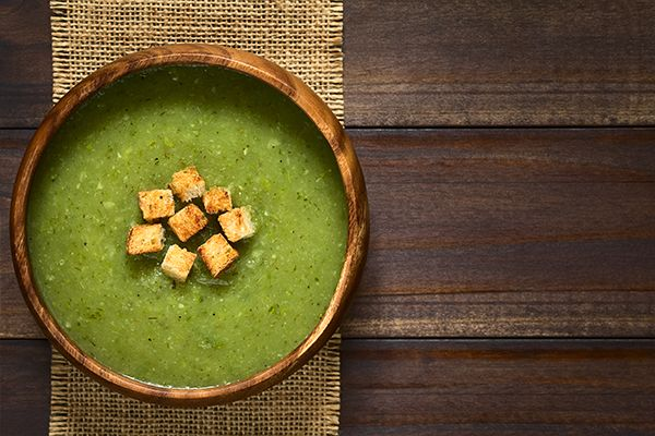 Eine grüne Zucchinisuppe mit Croûtons in einer Holzschüssel.