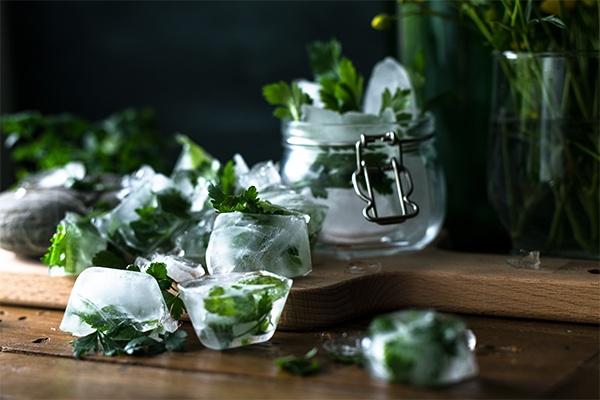 Ein Schneidebrett auf denen Kräuter Cubes liegen. Im Hintergrund ist ein Einmachglas gefüllt mit weiteren Kräuter Cubes.