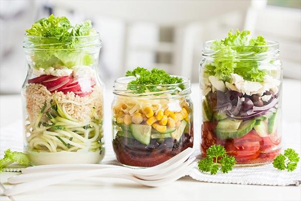 Drei gemischte bunte Salate in Einmachgläser.