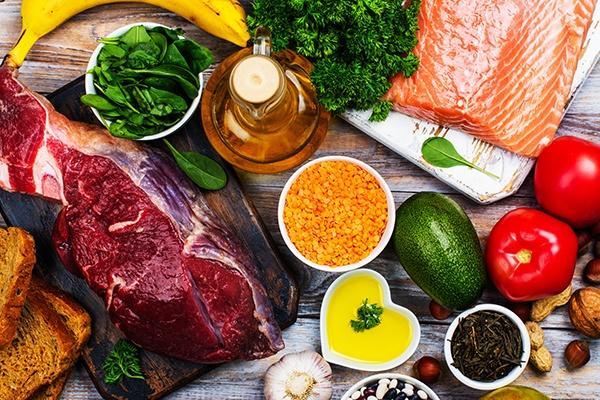 Auf einer Holzfläche liegen ein Stück Fleisch, mehrere Schüsseln gefüllt mit Linsen, Öl, Gewürzen und Salat. Auf einem Brett ist ein Lachsfilet. Daneben steht eine Flasche Öl.