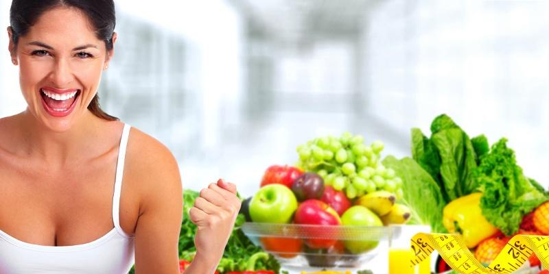 Eine Frau in weißem Trägershirt ballt motiviert die Fäuste. Im Hintergrund ist eine Schüssel mit Obst.