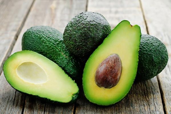Vier Avocados auf einer Holzfläche. Eine Frucht ist in zwei Hälften geteilt.