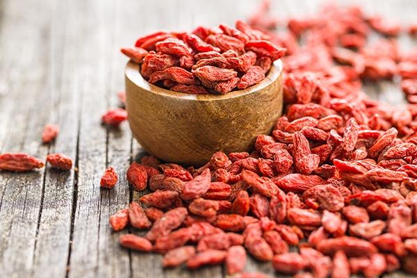 Eine kleine Holzschale mit roten Goji-Beeren. Daneben liegen noch weitere Beeren.