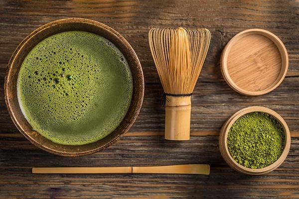 Eine Schale mit grünem Matcha, einem Bambusbesen, eine Holzdose mit grünem Matchapulver und einem Bambuslöffel liegen auf einer Holzfläche.