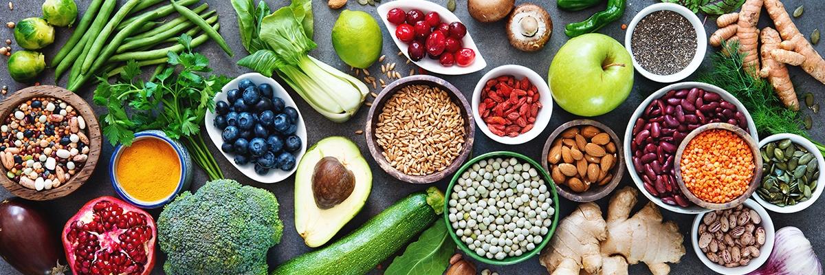 Unterschiedliches Superfood wie Obst, Gemüse und Schüsseln gefüllt mit Linsen sowie Bohnen stehen sind auf einer dunklen Fläche zu sehen.