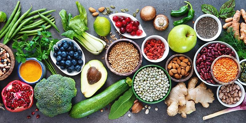 Ein aufgeschnittener Granatapfel, eine Schüssel mit Heidelbeeren, eine halbe Avocado und mehrere Schüsseln mit Linsen, Goji-Beeren und Mandeln.