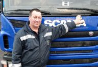 Ein LKW Fahrer legt die Hand auf die Motorhaube seines Trucks und lächelt in die Kamera.