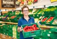 Eine HOFER Mitarbeiterin steht vor dem Obst- und Gemüseabteil und trägt eine grüne Kiste mit roten Paprikas.