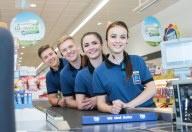 Vier junge Lehrlinge von HOFER stehen aufgereiht am Kassenband und lächeln in die Kamera.