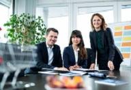 Ein Mann und zwei Frauen im Anzug sitzen oder stehen an einem Bürotisch und lächeln in die Kamera.