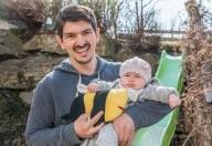 Ein Mann hält ein Baby und Bienenplüschtier. Er steht vor einer grünen Rutsche.