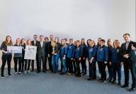 Eine große Reihe HOFER Mitarbeiter hält zwei Urkunden für 'Top Filialen 2018' nach oben.