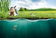 Kind auf Wiese vor einem Gewässer