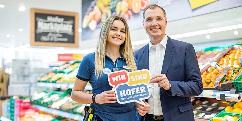 """HOFER-Generaldirektor Horst Leitner mit einer Mitarbeiterin vor dem Obstregal. Beide halten ein Schild mit der Aufschrift """"Wir sind HOFER""""."""