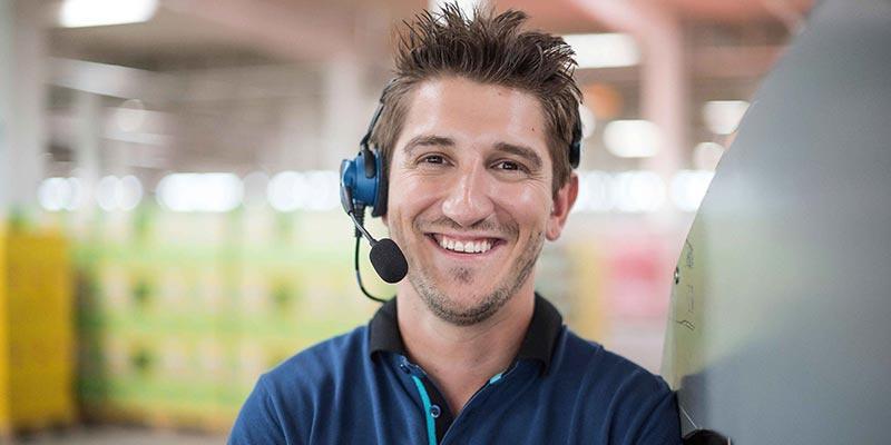 Ein HOFER-Logistik-Mitarbeiter mit Headset lächelt den Betrachter an.
