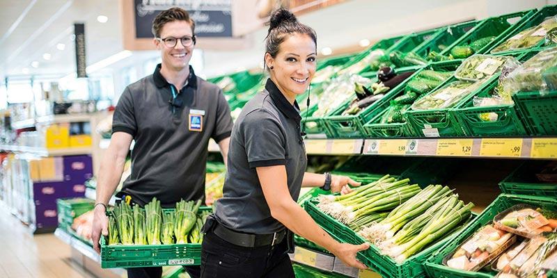 Zwei HOFER-Mitarbeiter räumen je eine Kiste mit Frühlingszwiebeln in das Gemüseregal.