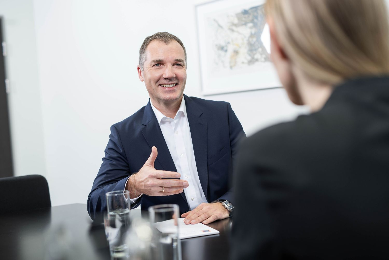 Generaldirektor Horst Leitner sitzt am Tisch im Gespräch mit einer Frau.