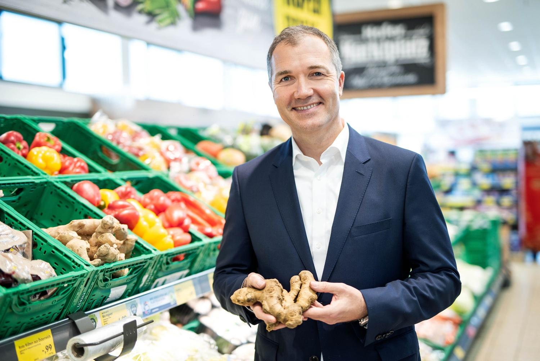 Generaldirektor Horst Leitner steht vor dem Gemüseregal einer HOFER-Filiale. Er lächelt in die Kamera und hält eine Ingwer in den Händen.