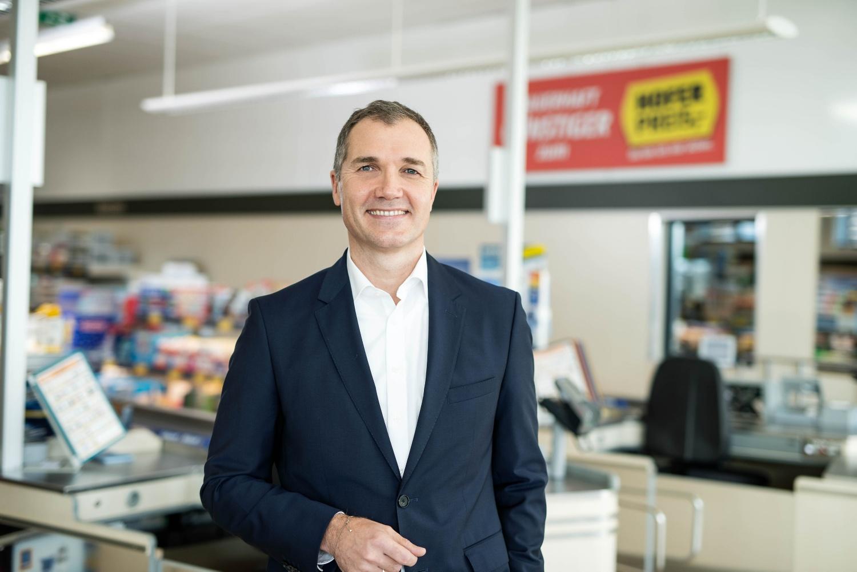 Generaldirektor Horst Leitner steht im Kassenbereich einer HOFER-Filiale. Er lächelt in die Kamera.