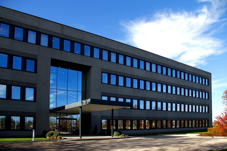 Der Eingangsbereich der HOFER-Hauptniederlassung in Sattledt. Ein modernes Gebäude mit einer großen Glasfront über dem Eingangsbereich.