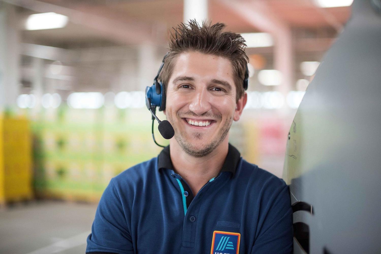Ein HOFER-Logistik-Mitarbeiter blickt lächelnd in die Kamera. er hat ein Headset mit Mikrofon am Kopf.