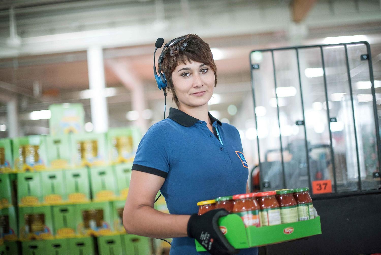 Eine HOFER-Logistik-Mitarbeiterin trägt einen Karton gefüllt mit Tomatensoße in Gläsern. Sie blickt in die Kamera. Auf ihrem koch hat sie ein Headset mit Mikrofon.