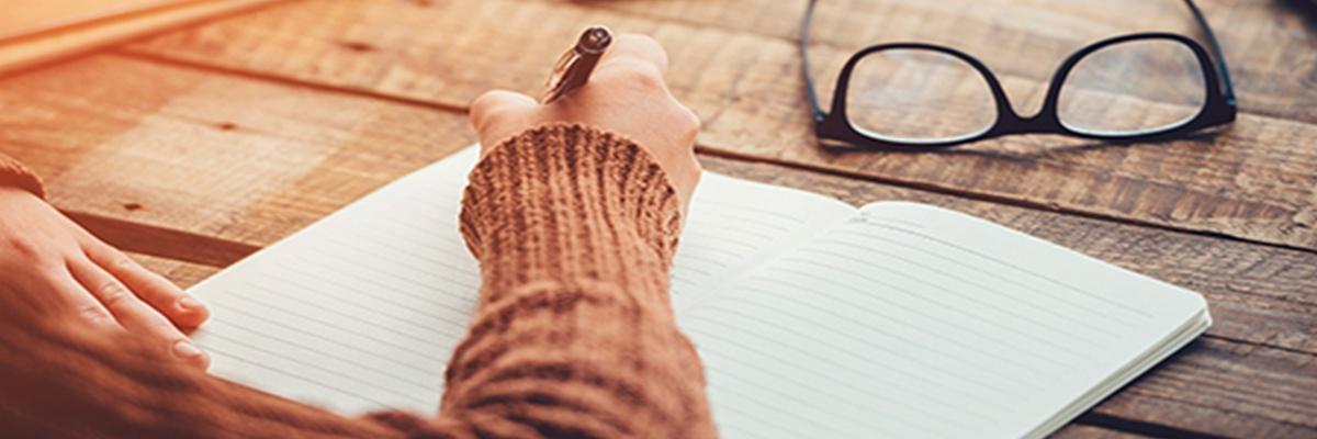 Eine Frau mit braunem Pullover schreibt in ein aufgeschlagenes unliniertes Heft. Auf dem Holztisch liegt eine schwarze Brille.