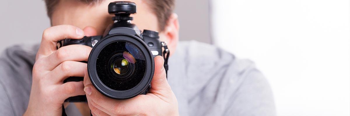 Ein Mann der den Betrachter mit einer Kamera fotografiert.