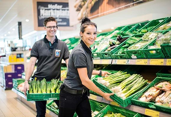 Zwei HOFER-Mitarbeiter räumen Kisten mit Frühlingszwiebeln in das Gemüseregal.