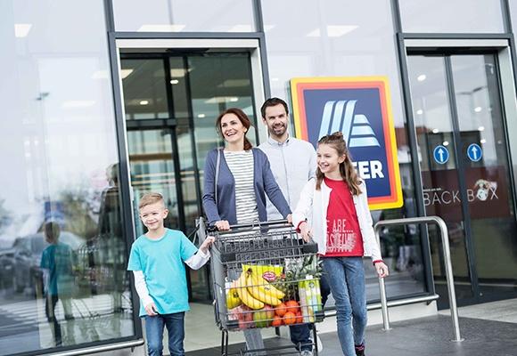 Eine vierköpfige Familie verlässt mit einem vollem Einkaufswagen eine HOFER-Filiale.