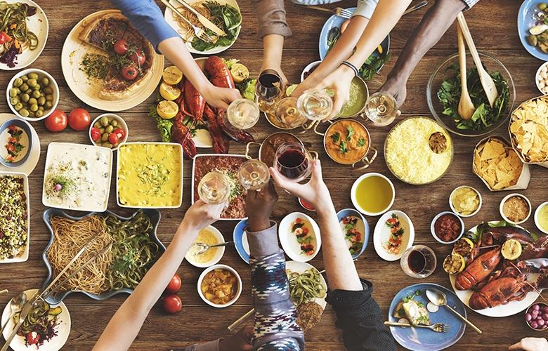 Sehr gut gefüllter Tisch mit vielen einzelnen Speisen sowie mehreren Armen, die gerade mit einem Getränk anstoßen.
