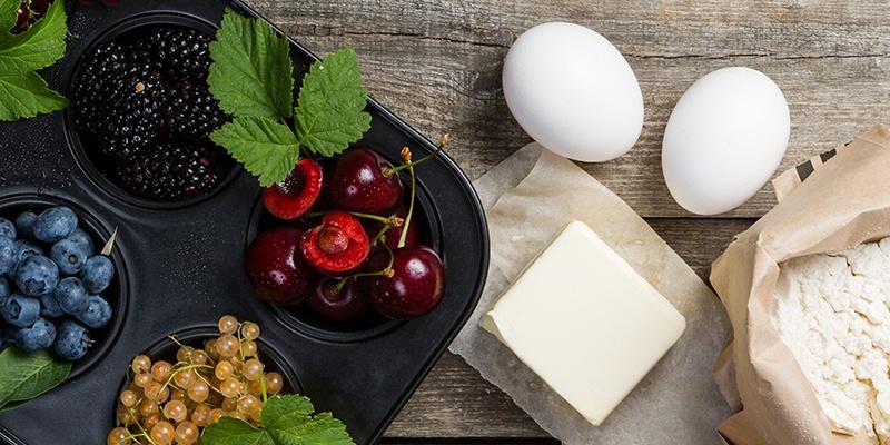 Backzutaten stehen auf einem rustikalen Tisch: Beeren wie Himbeeren, Heidelbeeren und Brombeeren sowie Eier, Butter und Mehl.