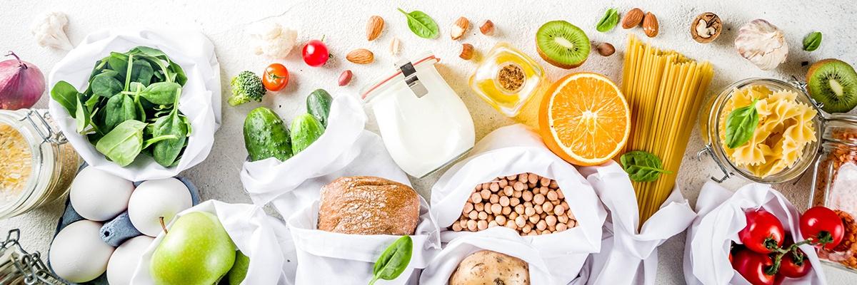 Ein Tisch voller gesund wirkender Lebensmittel wie Salat, Obst, Ölen, Eiern, Brot und Tomaten.