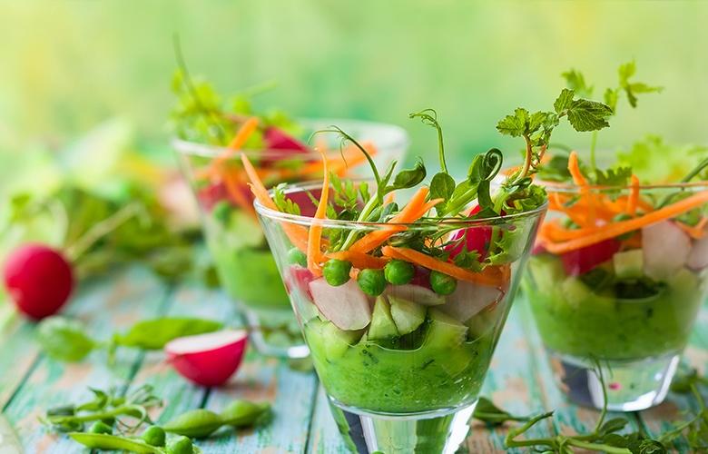 Kreativer Salat in ausgefallener Salatschale, der Radieschen, Möhrenstreifen, Erbsen sowie einen grünen Smoothie enthält.