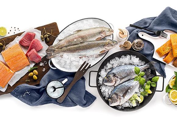 Aufgeschnittener Frisch wie Lachs und Thunfisch liegen auf einem Holzschneidebrett. Ganzer Fisch liegt gekühlt auf Eiswürfeln. Zitronen und Gewürze runden das Bild ab.