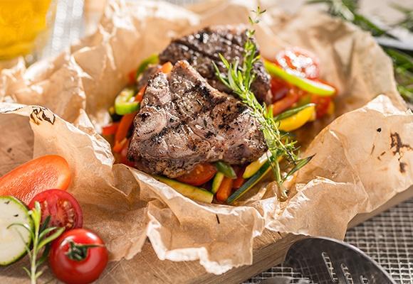 Saftig-zartes Fleisch liegt auf buntem Gemüse und wurde mediterran zubereitet.