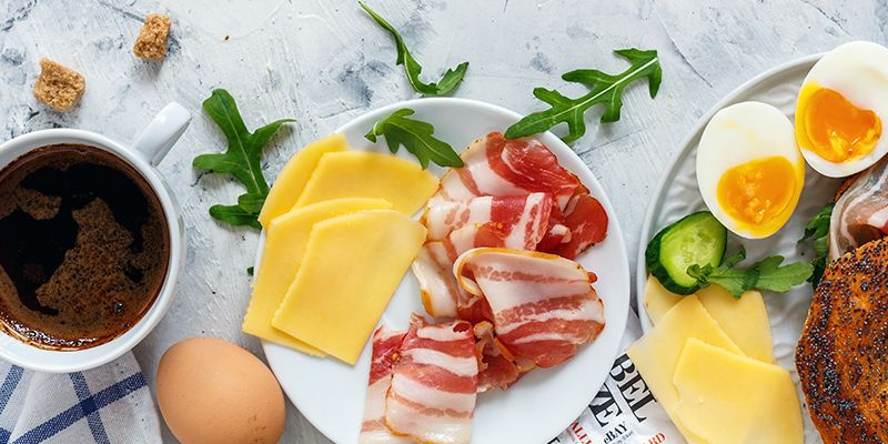 Buntes Frühstück mit Kaffee, Käse, Wurst, Ei und Mohnbrötchen steht auf rustikalem Holzuntergrund.