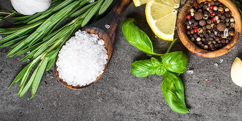Kräuter, ein Holzlöffel mit groben Salz, Basilikum und ein Schälchen mit buntem Pfeffer auf grauem Hintergrund.