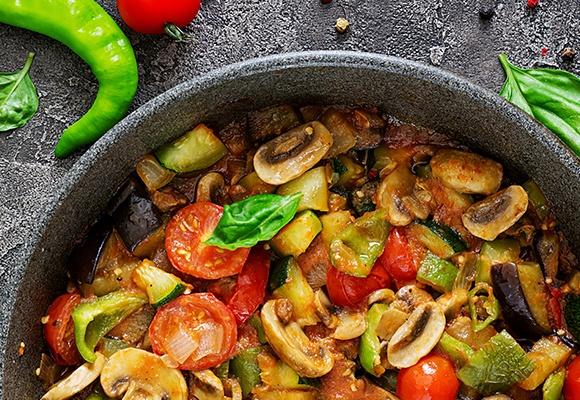 Eine bunte Gemüsepfanne mit Tomaten, Zucchini und Pilzen.