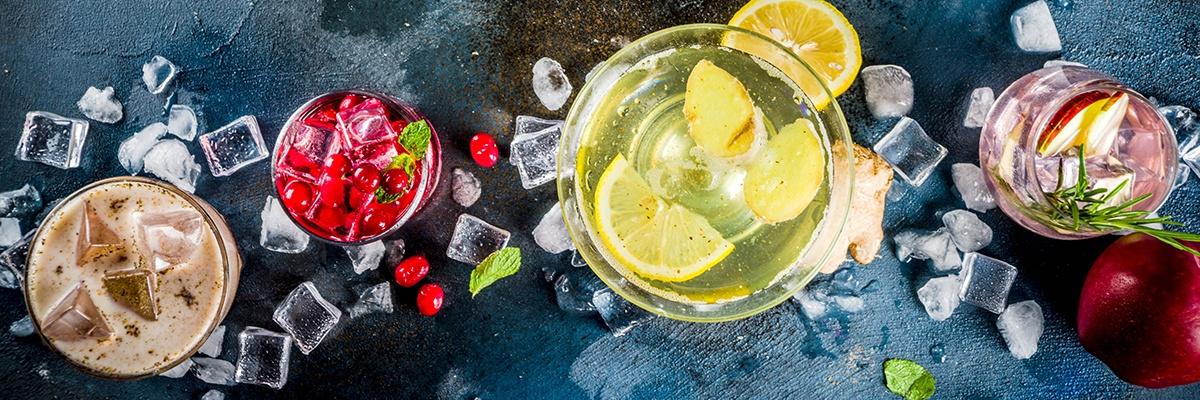 Vier bunte Getränke werden von oben gezeigt, um sie herum liegen Eiswürfel. Sie sind mit verschiedenen Früchten wie Zitronen und Cranberrys gefüllt.
