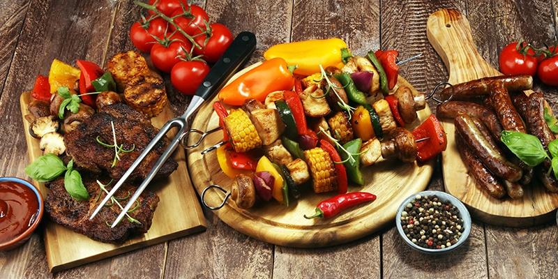 Grillspieße, Steaks und Würstchen liegen auf Holzbrettchen.