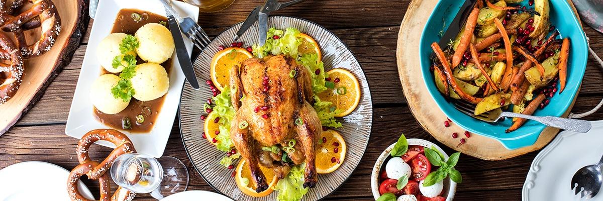 Ein Teller mit einer gebratenen Ente, daneben ein blauer Teller mit Gemüse. Auf einem Teller links sind vier Knödel mit brauner Soße.
