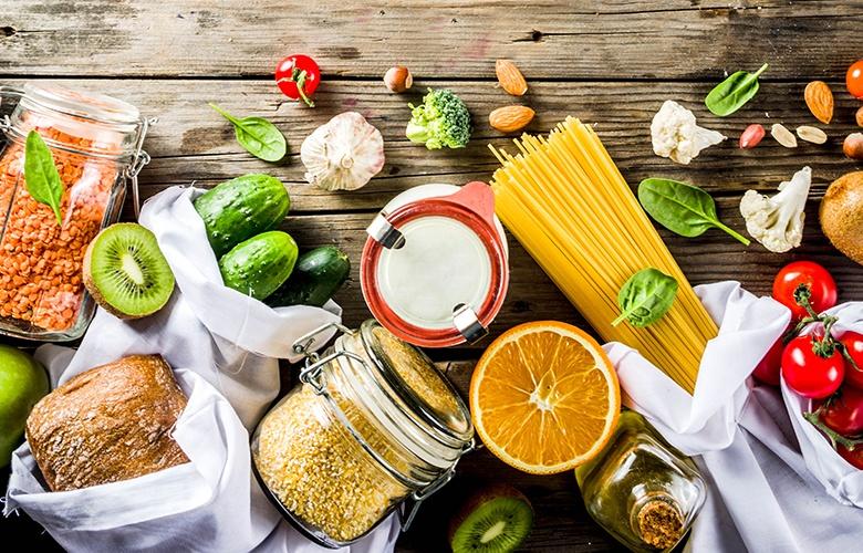 Verschiedene Zutaten auf einem Holztisch wie rohe Nudeln, Tomaten, Brot, Reis und Kiwi sowie Knoblauch.