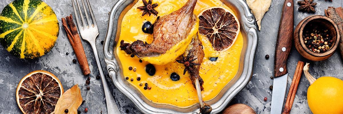 Orange Kürbissuppe rustikal serviert mit zwei Entenkeulen.