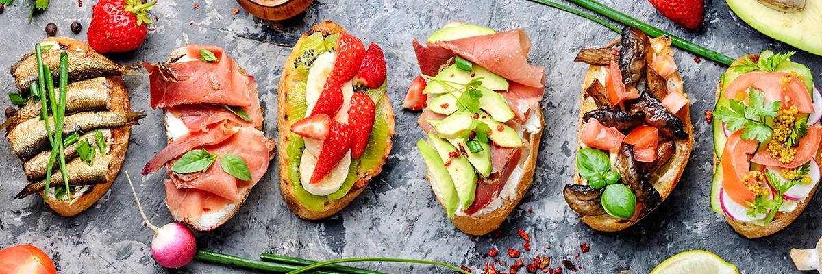 Sechs bunte Brote sind mit verschiedenen Lebensmitteln belegt: Fisch, Wurst, Obst, Gemüse und Pilze.