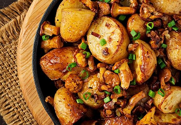 Gebratene Kartoffeln mit Frühlingszwiebeln und Pilzen liegen in einer Pfanne.