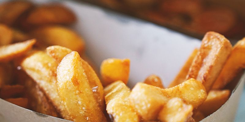 Goldbraune Pommes verzehrbereit in einem Pappbehälter.