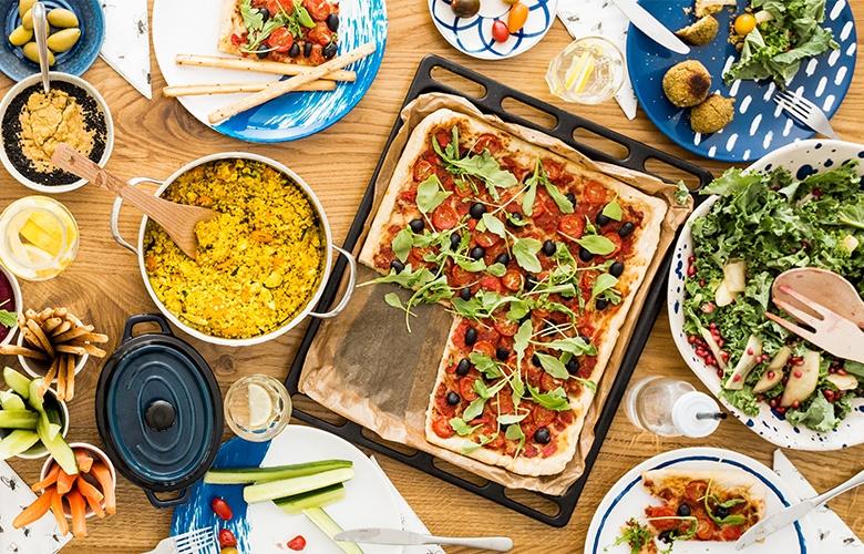 Großes mediterranes Menü mit selbstgemachten Speisen wie Pizza und Salat.
