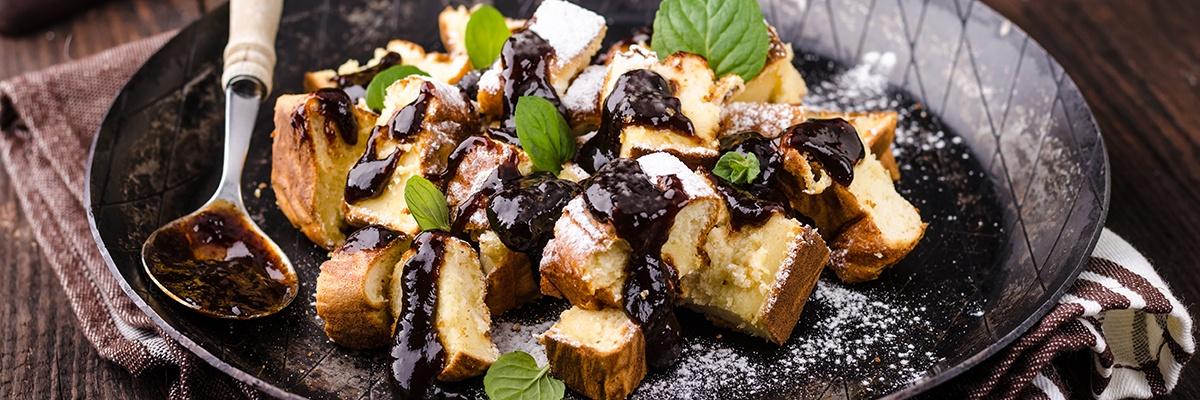Süßer Teig bestreut mit Puderzucker und Schokoladensoße.