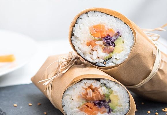 Maki Sushi: Klebereis ist eingerollt in einem Noriblatt und Papier. Es liegt auf einer Steinplatte.